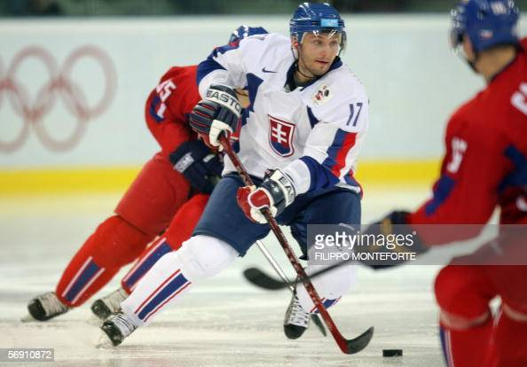 Slovak Lubomir Visnovsky controls the puck between Czech Rotislav Olesz and Czech Petr Janek during the ice hockey men's preliminary game Slovakia vs...