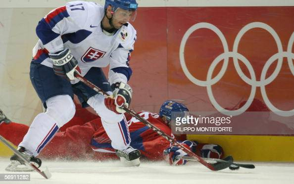 Slovak Lubomir Visnovsky fights fot the puck with Czech Jan Bulis during the ice hockey men's preliminary game Slovakia vs Czech Republic at the 2006...