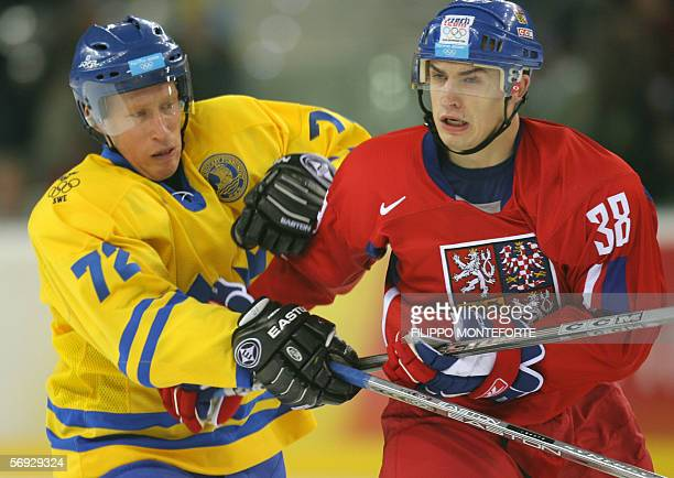 Swedish Jorgen Jonsson vies with Czech Jan Bulis during the 2006 Winter Olympic ice hockey men's semifinal game between Sweden and Czech Republic 24...