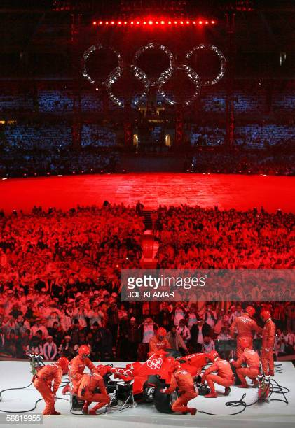 Technicians assemble a Ferrari on stage during the opening ceremonies of the 2006 Winter Olympics 10 February 2006 in Turin Italy AFP PHOTO JOE KLAMAR