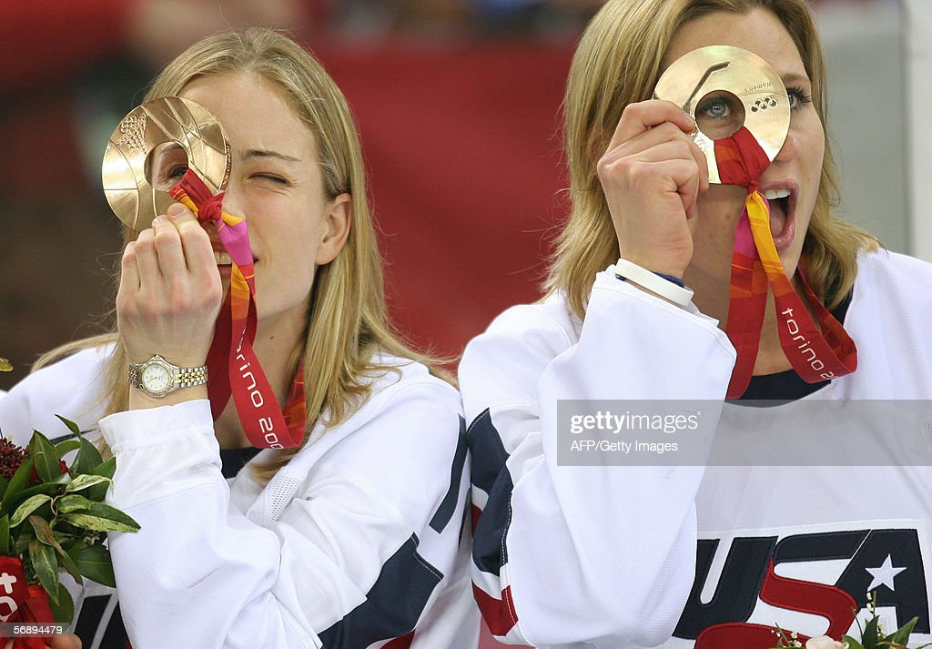 US Jamie Hagerman (L) and Angela Ruggiero look threw their bronze medals during the medal ceremony at the 2006 Winter Olympics,, 20 February 2006 at the Palasport Olimpico in Turin.