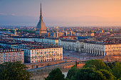 Aerial cityscape image of Turin, Italy during summer sunrise.
