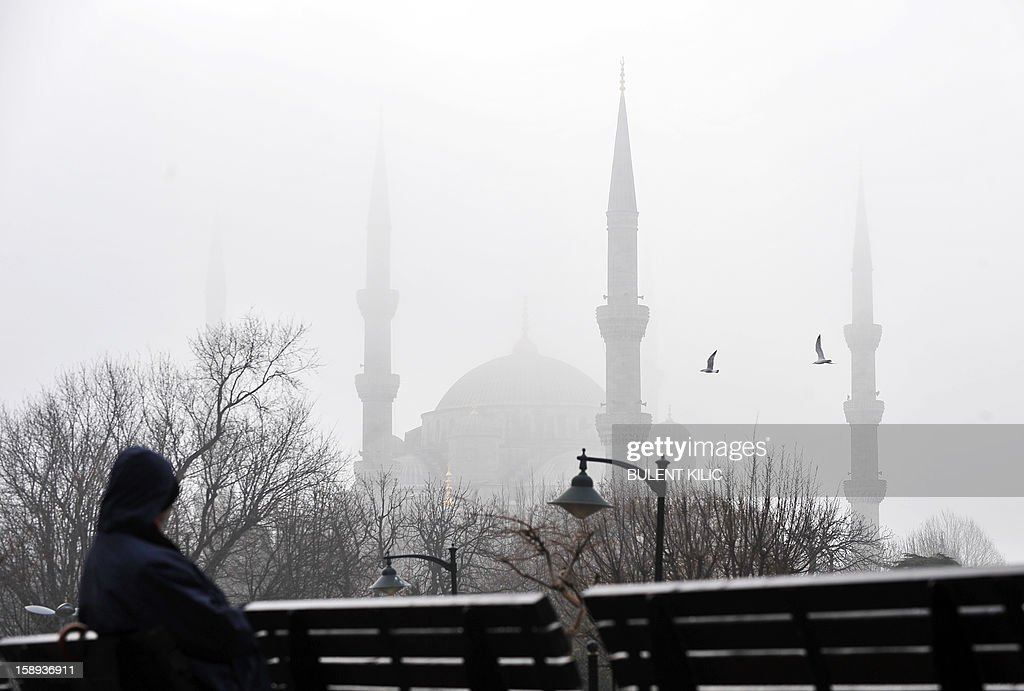 A Turk sits at Sultanahmet square in a heavy fog on January 4, 2013, in Istanbul. AFP PHOTO/BULENT KILIC
