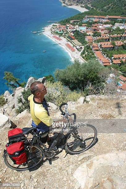 A man is taking a break during his bicycle tour in the mountains