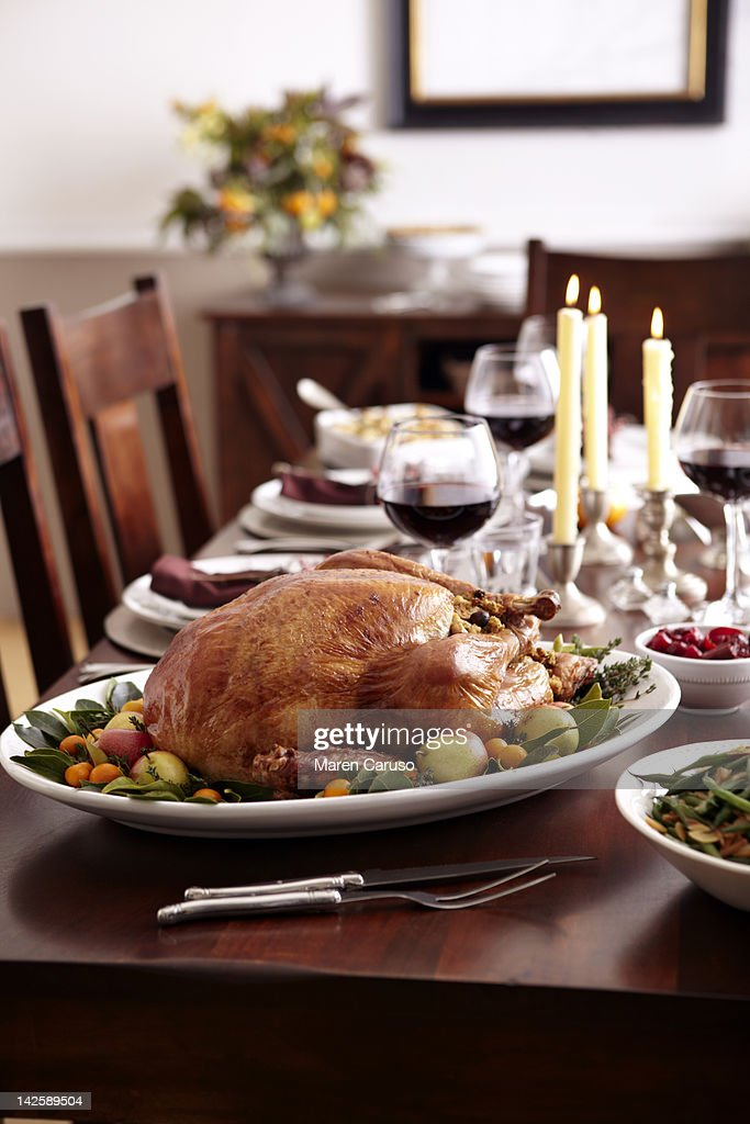 Turkey and holiday dishes on table with candles : Stock Photo