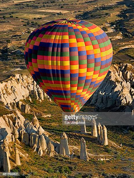 Turkey Cappadocia Goreme Brightly colored hot air balloon in flight over rock peaks and pinnacles of Love Valley in early morning