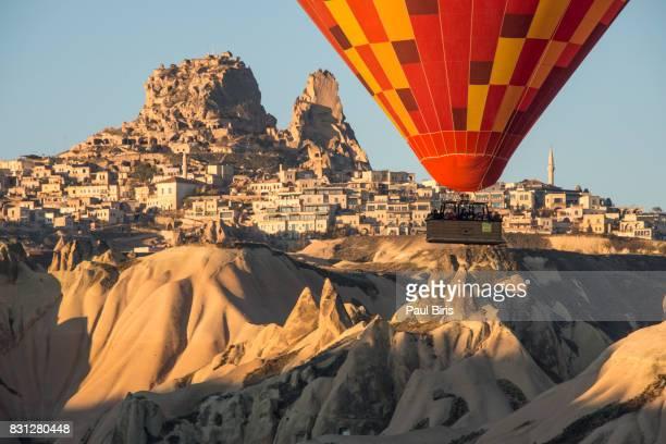 Turkey, Central Anatolia, Cappadocia, Hot air balloon flying over Uchisar Castle near Goreme