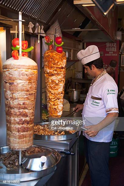 Turkey Istanbul Sultanahmet man in kebab restaurant carving shawarma from skewered meats
