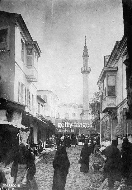 people in a lane a mosque in the background probably in the 1910s