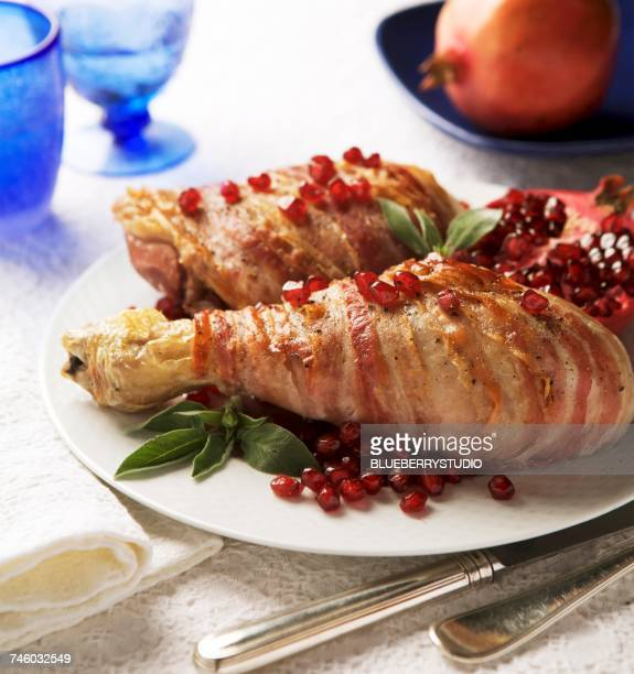 Turkey legs wrapped in bacon with pomegranate seeds and sage