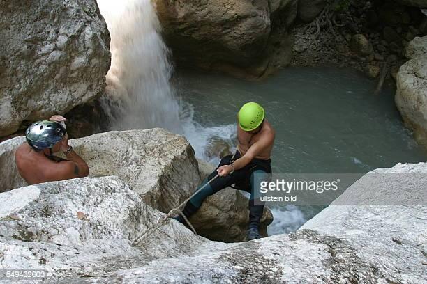 Men during a climbing tour at a mountain lake