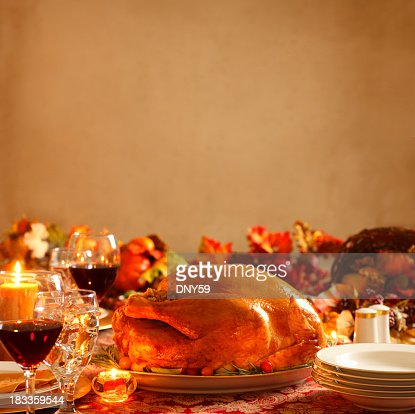 Turkey on platter in a Thanksgiving dinner setting