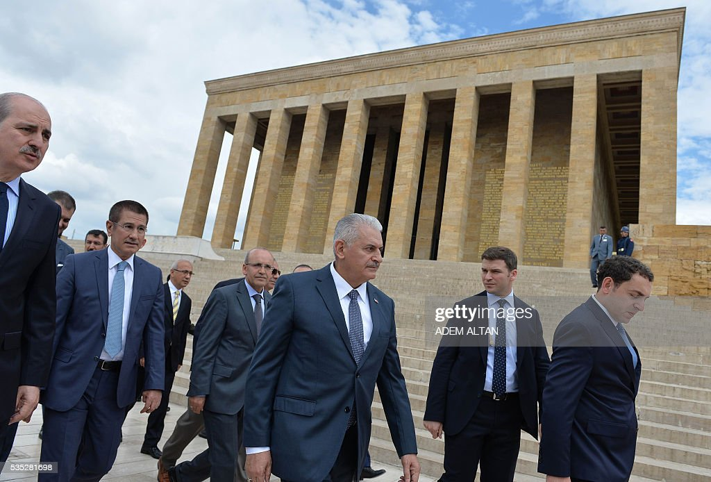 Turkey Prime Minister Binali Yildirim (C) and ministers of the new cabinet visit the mausoleum of Turkey's first president-Mustafa Kemal Ataturk on May 29, 2016 in Ankara. Turkey's new government led by a staunch ally of President Recep Tayyip Erdogan easily passed a confidence vote in the country's parliament on May 29, the speaker announced after the vote. Binali Yildirim, who replaced Ahmet Davutoglu as prime minister last week, was backed by 315 parliamentarians while 138 voted against, parliament speaker Ismail Kahraman said after the ballot. / AFP / ADEM