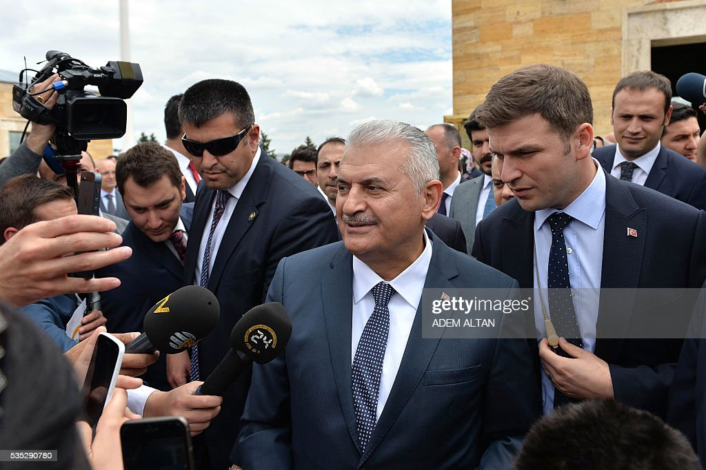 Turkey Prime Minister Binali Yildirim (C) answers jounalists' questions during a visit to the mausoleum of Turkey's first president-Mustafa Kemal Ataturk on May 29, 2016 in Ankara. Turkey's new government led by a staunch ally of President Recep Tayyip Erdogan easily passed a confidence vote in the country's parliament on May 29, the speaker announced after the vote. Binali Yildirim, who replaced Ahmet Davutoglu as prime minister last week, was backed by 315 parliamentarians while 138 voted against, parliament speaker Ismail Kahraman said after the ballot. / AFP / ADEM