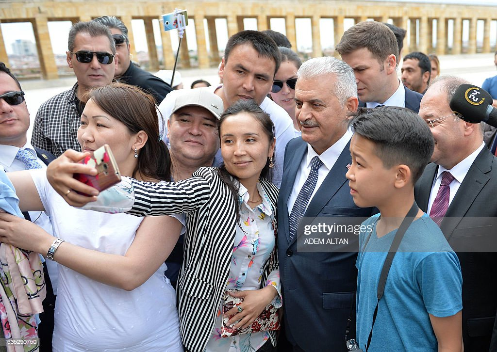 Turkey Prime Minister Binali Yildirim (R) poses for a selfie picture with a woman during a visit to the mausoleum of Turkey's first president-Mustafa Kemal Ataturk on May 29, 2016 in Ankara. Turkey's new government led by a staunch ally of President Recep Tayyip Erdogan easily passed a confidence vote in the country's parliament on May 29, the speaker announced after the vote. Binali Yildirim, who replaced Ahmet Davutoglu as prime minister last week, was backed by 315 parliamentarians while 138 voted against, parliament speaker Ismail Kahraman said after the ballot. / AFP / ADEM