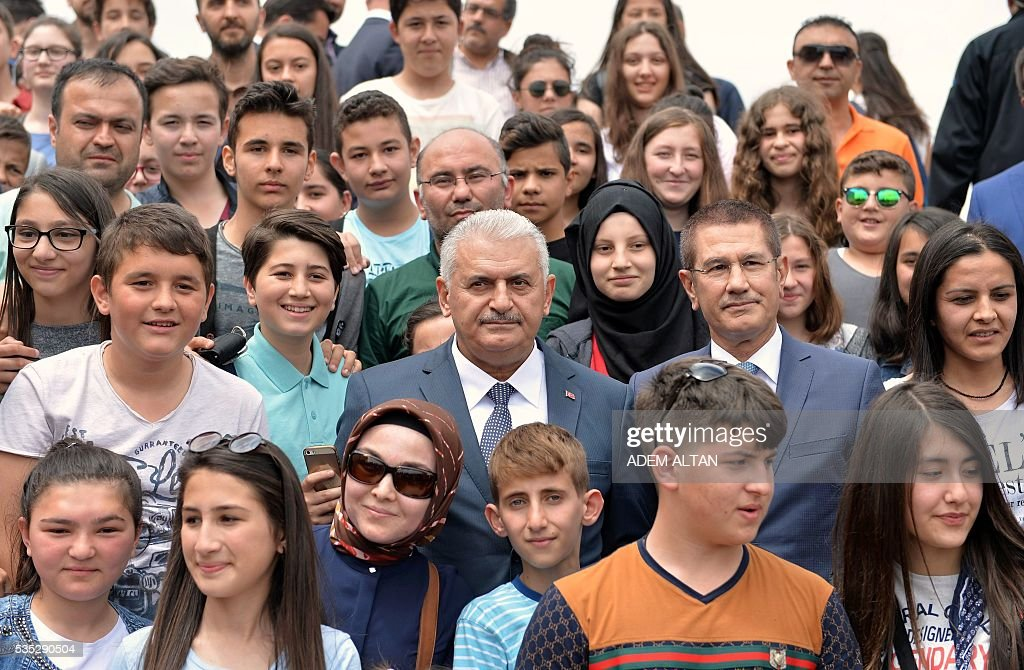 Turkey Prime Minister Binali Yildirim (C) poses with children during a visit to the mausoleum of Turkey's first president-Mustafa Kemal Ataturk on May 29, 2016 in Ankara. Turkey's new government led by a staunch ally of President Recep Tayyip Erdogan easily passed a confidence vote in the country's parliament on May 29, the speaker announced after the vote. Binali Yildirim, who replaced Ahmet Davutoglu as prime minister last week, was backed by 315 parliamentarians while 138 voted against, parliament speaker Ismail Kahraman said after the ballot. / AFP / ADEM