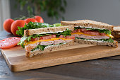 Turkey, Cheese, Tomato Sandwich with Lettuce on a Cutting Board