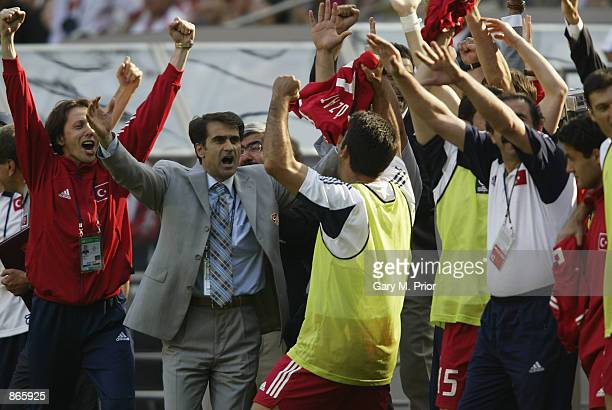 Turkey soccer coach Senol Gunes celebrates with his players after Turkey beat China 30 and qualify for the second stage of the World Cup during the...