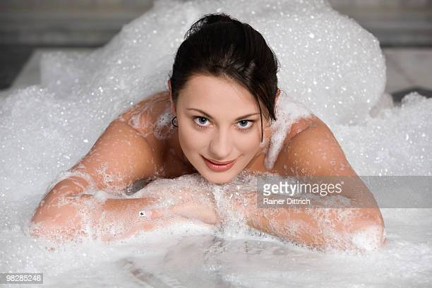 Turkey, Young woman having bubble bath, smiling, portrait