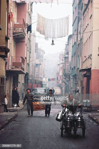Turkey,Istanbul,man on tricycle,people carrying food crate in street