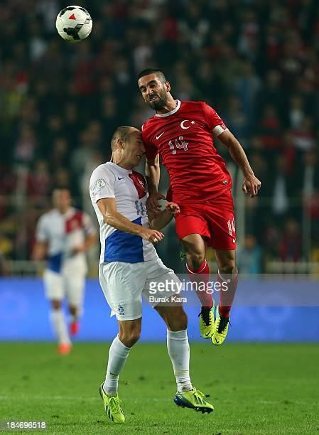Turkey's Arda Turan jumps for a header over Arjen Roben of Netherlands during FIFA 2014 World Cup Qualifier match at the Sukru Saracoglu Stadium on...