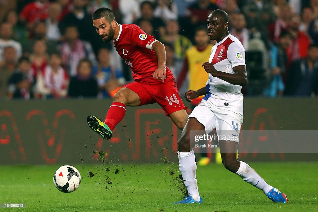Turkey's Arda Turhan kicks the ball past <a gi-track='captionPersonalityLinkClicked' href=/galleries/search?phrase=Jeremain+Lens&family=editorial&specificpeople=4174305 ng-click='$event.stopPropagation()'>Jeremain Lens</a> of Netherlands during FIFA 2014 World Cup Qualifier match at the Sukru Saracoglu Stadium on October 15, 2013 in Istanbul, Turkey.