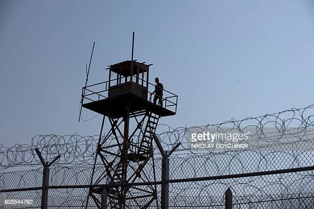 A Turkey's border police personel stands on a watchtower overlooking a barbed wire wall fence erected on the BulgariaTurkey border near the town of...