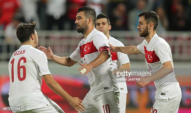 Turkey's captain Arda Turan is congratulated by teammates after his goal during their friendly football match against Qatar in the capital Doha on...