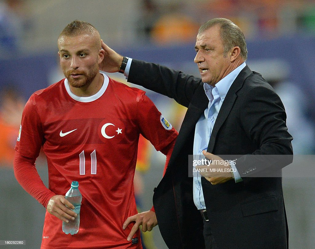 Turkey's Coach Fatih Terim (R) greets Gokhan Tore during the FIFA World Cup 2014 qualifying football match Romania vs Turkey in Bucharest on September 10, 2013. AFP PHOTO / DANIEL MIHAILESCU