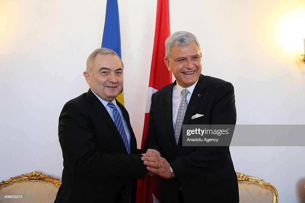 Turkey's EU Minister Volkan Bozkir (R) and Romanian Foreign Minister Lazar Comanescu (L) shkae hands as they meet in Bucharest, Romania on February 11, 2016.