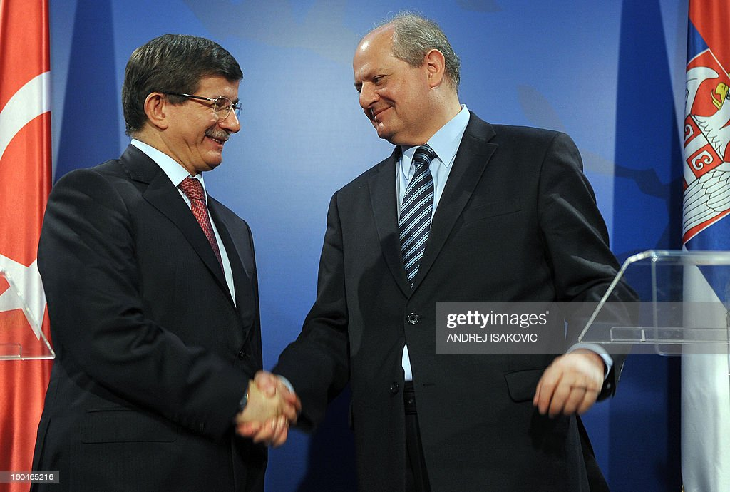 Turkey's Foreign Minister Ahmet Davutoglu (L) shakes hand with his Serbian counterpart Ivan Mrkic at a press conference following their meeting in Belgrade on February 1, 2013. AFP PHOTO / ANDREJ ISAKOVIC