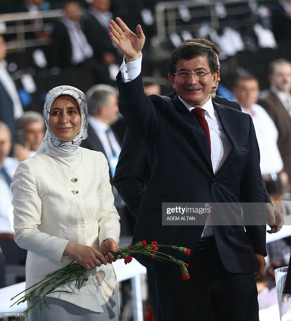 Turkey's Foreign Minister Ahmet Davutoglu waves next to his wife Sare Davutoglu during the Extraordinary Congress of the ruling Justice and Development Party (AKP) in Ankara on August 27, 2014. Davutoglu was approved by the ruling Justice and Development Party (AKP) as its new leader and prime minister to take over when Recep Tayyip Erdogan moves to the presidency on August 28, 2014.