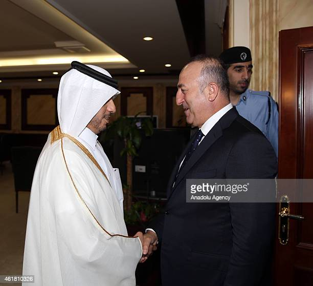 Turkey's Foreign Minister Mevlut Cavusoglu shakes hands with Qatari Prime Minister Abdullah bin Nasser bin Khalifa Al Thani during his official visit...