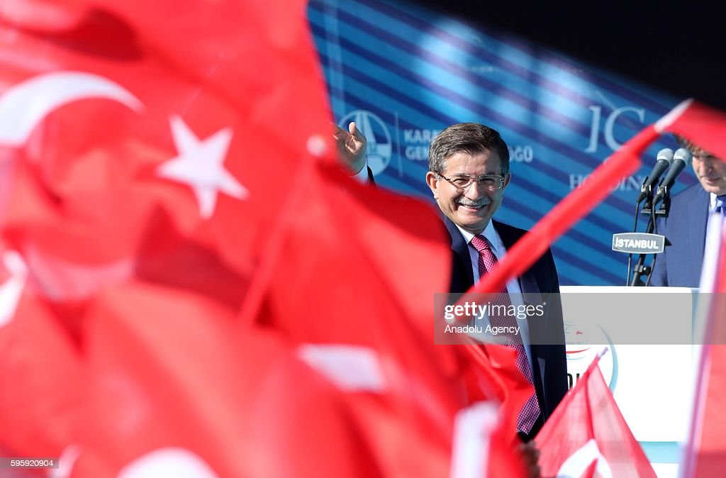 Turkey's Former Prime Minister and ruling Justice and Development Party's Konya Deputy Ahmet Davutoglu greets people as they attend the opening...