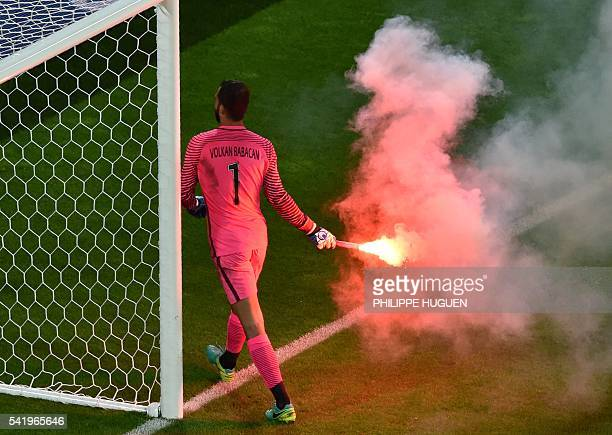 Turkey's goalkeeper Volkan Babacan removes a flare from the pitch during the Euro 2016 group D football match between Czech Republic and Turkey at...