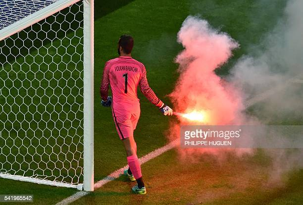 Turkey's goalkeeper Volkan Babacan takes a flare away from the pitch during the Euro 2016 group D football match between Czech Republic and Turkey at...