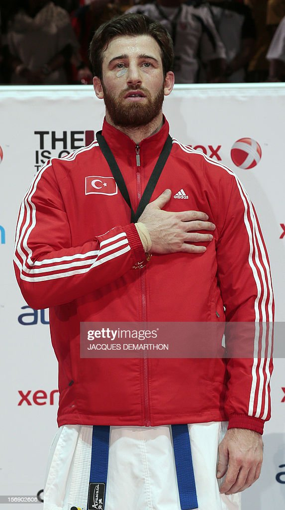 Turkey's gold medalist Enes Erkan listens to his national anthem on the podium of the Male Kumite over 84kg category at the Karate world championships on November 24, 2012 in Paris.