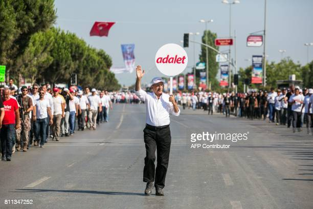 Turkey's main opposition Republican People's Party leader Kemal Kilicdaroglu holding a placard that reads 'Justice' gestures as he walks with...