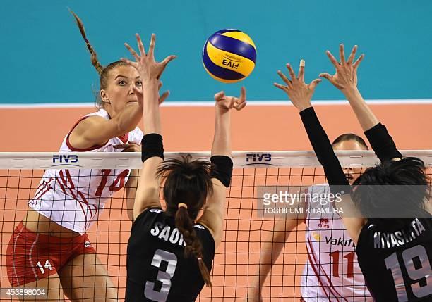 Turkey's Meliha Ismailoglu spikes the ball past captain Saori Kimura and Haruka Miyashita during their women's volleyball World Grand Prix final...