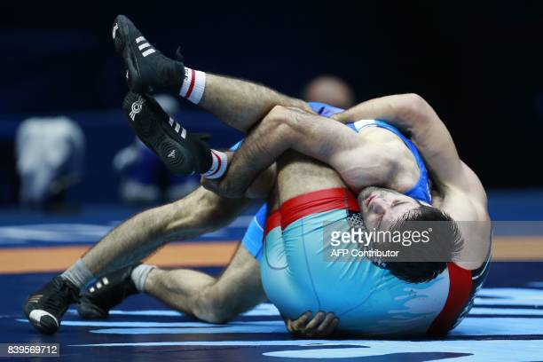 Turkey's Mustafa Kaya challenges Russia's Alan Gogaev during the men's freestyle wrestling 65kg category bronze medal final at the FILA World...