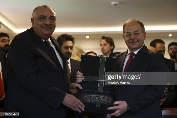Turkey's new Deputy Prime Minister Recep Akdag takes over his new post from Tugrul Turkes during a handover ceremony following Turkish Cabinet...