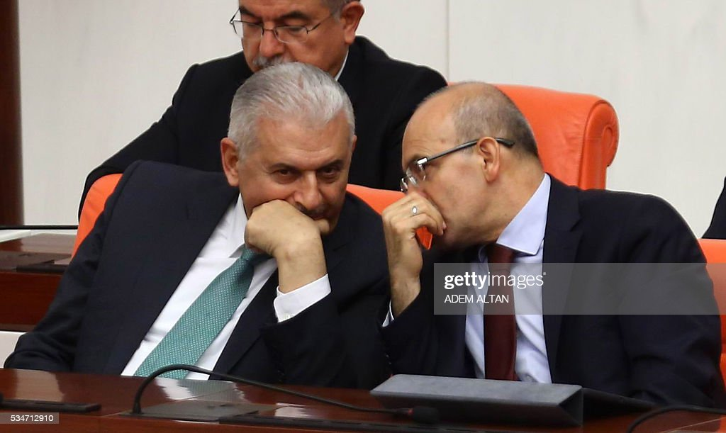 Turkey's new Prime Minister Binali Yildirim (L) and Turkish Deputy Prime Minister Yildirim Tugrul Turkes (R) attend the general session at the Grand National Assembly of Turkey (TBMM) in Ankara on May 27, 2016. / AFP / ADEM