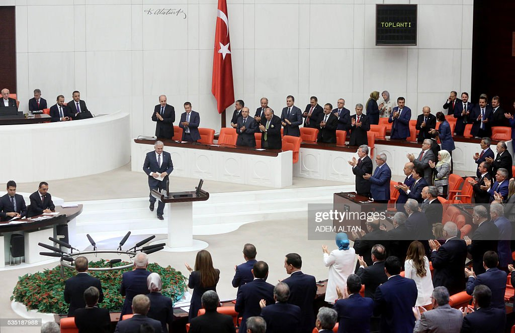 Turkey's new Prime Minister Binali Yildirim(C) is applauded as he arrives at the general session at Grand National Assembly of Turkey (TBMM) in Ankara, Turkey on May 29, 2016. Turkeys new government won a parliamentary vote of confidence with ruling Justice and Development Party (AKP) Chairman and Prime Minister Binali Yildirims government receiving 315 votes, while 138 lawmakers voted against the administration. / AFP / ADEM