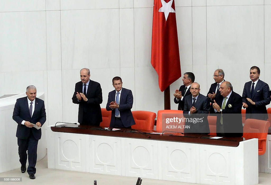 Turkey's new Prime Minister Binali Yildirim (L) is applauded as he arrives at the general session at Grand National Assembly of Turkey (TBMM) in Ankara, Turkey on May 29, 2016. Turkeys new government won a parliamentary vote of confidence with ruling Justice and Development Party (AKP) Chairman and Prime Minister Binali Yildirims government receiving 315 votes, while 138 lawmakers voted against the administration. / AFP / ADEM