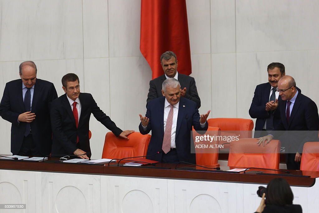 Turkey's new Prime Minister Binali Yildirim (C) is applauded by his ministers as he arrives to read his government's programm at the Turkish parliament in Ankara, on May 24, 2016. / AFP / ADEM