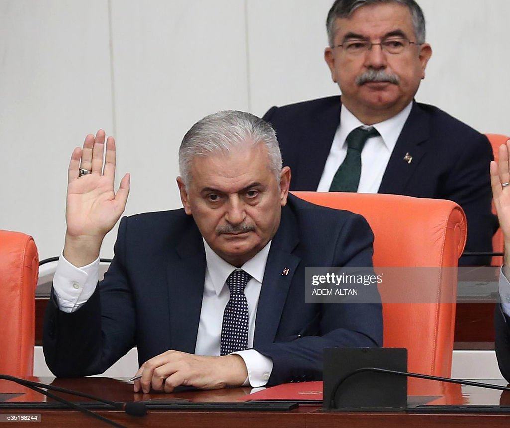 Turkey's new Prime Minister Binali Yildirim (Foreground) raises his hand during the general session at the Grand National Assembly of Turkey (TBMM) in Ankara, Turkey on May 29, 2016. Turkeys new government won a parliamentary vote of confidence with ruling Justice and Development Party (AKP) Chairman and Prime Minister Binali Yildirims government receiving 315 votes, while 138 lawmakers voted against the administration. / AFP / ADEM