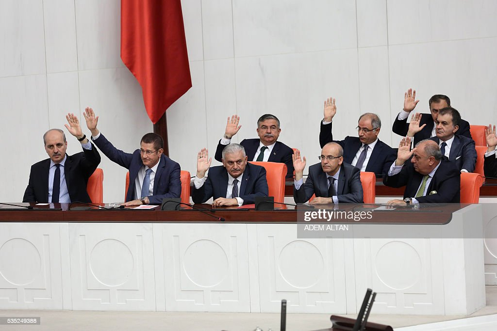 Turkey's new Prime Minister Binali Yildirim (C) raises his hand while seated during the general session at the Grand National Assembly of Turkey (TBMM) in Ankara, Turkey on May 29, 2016. Turkeys new government won a parliamentary vote of confidence with ruling Justice and Development Party (AKP) Chairman and Prime Minister Binali Yildirims government receiving 315 votes, while 138 lawmakers voted against the administration. / AFP / ADEM