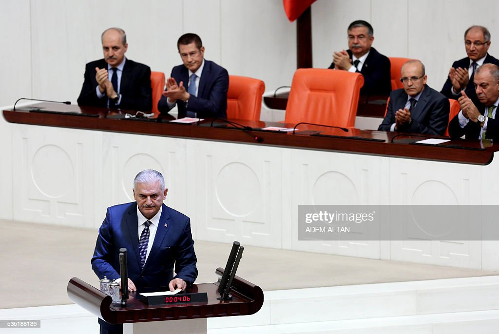 Turkey's new Prime Minister Binali Yildirim (Foreground) takes to the podium at the general session at Grand National Assembly of Turkey (TBMM) in Ankara, Turkey on May 29, 2016. Turkeys new government won a parliamentary vote of confidence with ruling Justice and Development Party (AKP) Chairman and Prime Minister Binali Yildirims government receiving 315 votes, while 138 lawmakers voted against the administration. / AFP / ADEM