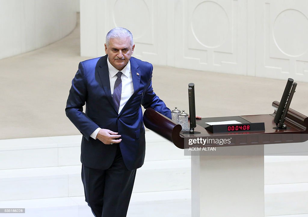 Turkey's new Prime Minister Binali Yildirim (Foreground) walks from the podium at the general session at the Grand National Assembly of Turkey (TBMM) in Ankara, Turkey on May 29, 2016. Turkeys new government won a parliamentary vote of confidence with ruling Justice and Development Party (AKP) Chairman and Prime Minister Binali Yildirims government receiving 315 votes, while 138 lawmakers voted against the administration. / AFP / ADEM