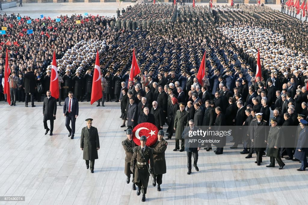 Turkey's President Recep Tayyip Erdogan (C) follows Turkish military carrying a	spray of flowers depecting the symbols of Turkish national flag, as he arrives to attend a ceremony marking the 79th death anniversary of Mustafa Kemal Ataturk, founder of modern Turkey, at the mausoleum for Ataturk, in Ankara, on November 10, 2017. /